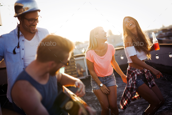 Having a great time with friends, havinf fun at rooftop party - Stock Photo - Images