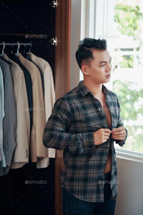 Dressing young man at home in morning - Stock Photo - Images