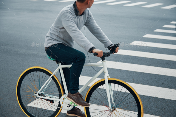 Crop guy listening to music and riding bicycle - Stock Photo - Images