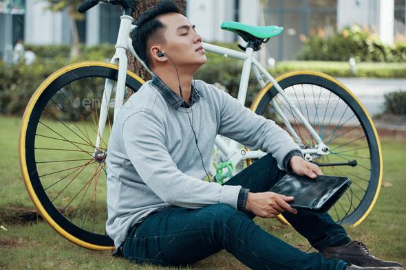 Asian male enjoying music near bicycle - Stock Photo - Images