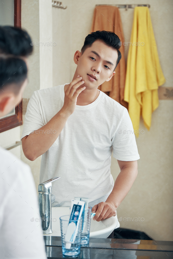 Young man grooming in bathroom mirror - Stock Photo - Images