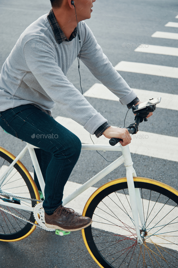 nonymous man in earphones riding bike near crosswalk - Stock Photo - Images