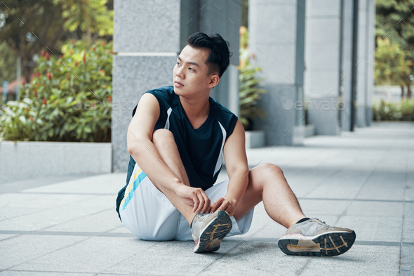 Asian man tying laces on sneakers - Stock Photo - Images