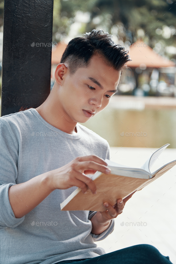 Asian man reading book on street - Stock Photo - Images