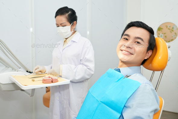 Smiling ethnic man in dental chair - Stock Photo - Images