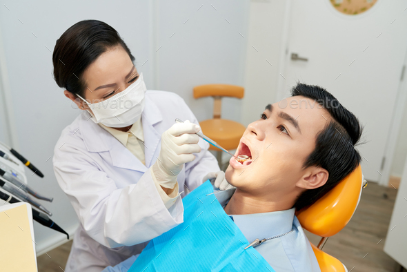 Professional dentist checking health of ethnic man - Stock Photo - Images