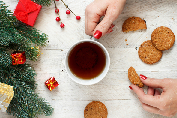 Christmas composition with hands keeping tea mug and cookies - Stock Photo - Images