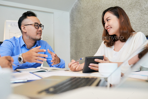 Ethnic colleagues discussing report at table - Stock Photo - Images