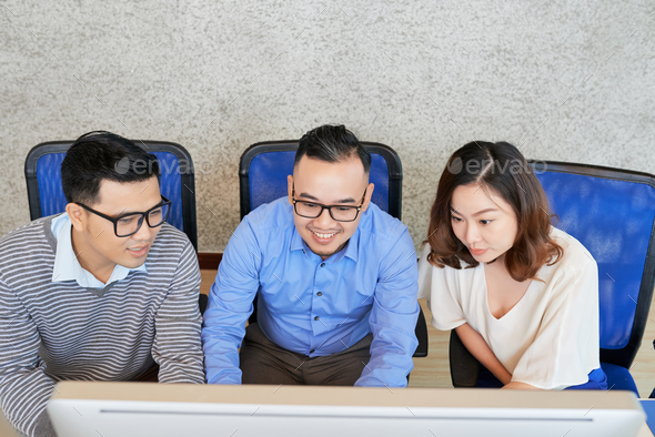 Young employees working with computer in team - Stock Photo - Images