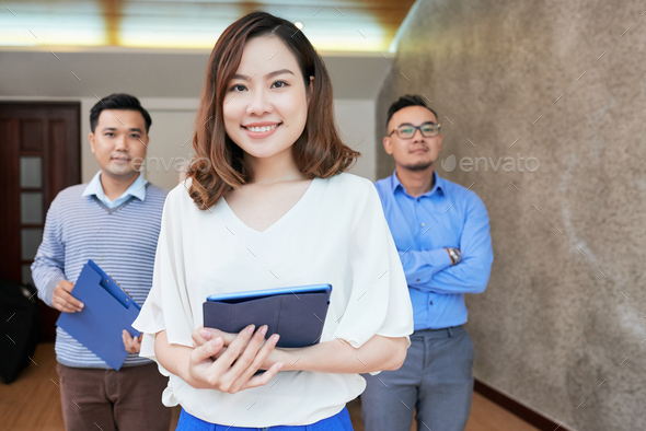 Beautiful ethnic woman with coworkers looking at camera - Stock Photo - Images