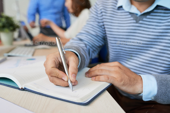 Crop casual man writing in notepad - Stock Photo - Images
