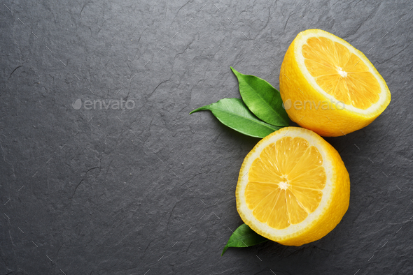 Two halved lemons with leaves on black slate background - Stock Photo - Images