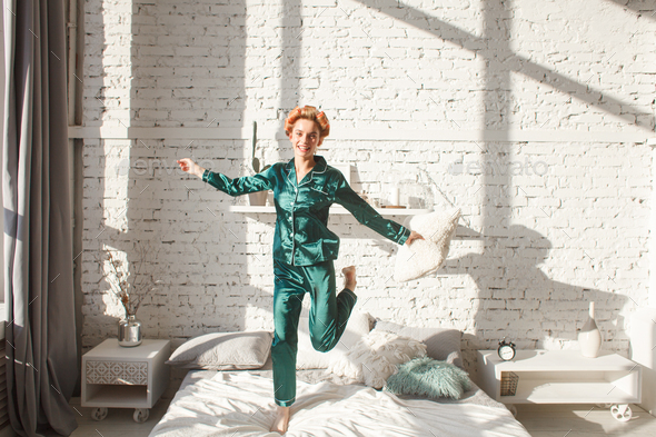 cheerful girl in nightwear jumping on bed - Stock Photo - Images