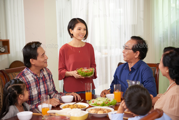 Housewife bringing dish to table - Stock Photo - Images