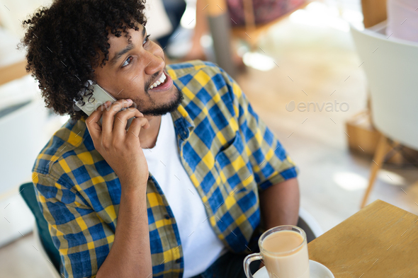 Handsome hipster man with beard in town calling on mobile phone - Stock Photo - Images