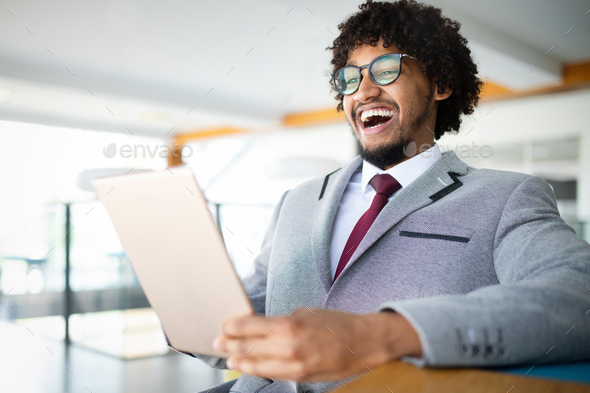 Smiling portrait of black businessman with touchscreen tablet device in office - Stock Photo - Images