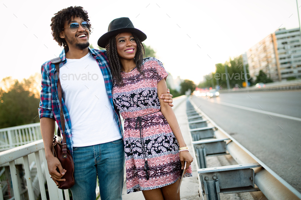 Couple of tourists taking a walk in a city street sidewalk in a sunny day - Stock Photo - Images
