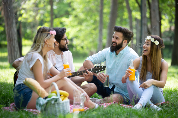 Happy friends in the park having picnic on a sunny day - Stock Photo - Images