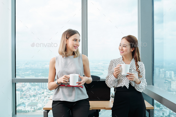 Female colleagues enjoying short break - Stock Photo - Images