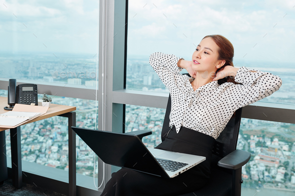 Businesswoman leaning back in her chair - Stock Photo - Images