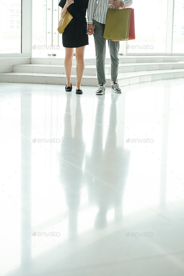 Couple walking in mall with paper-bags - Stock Photo - Images