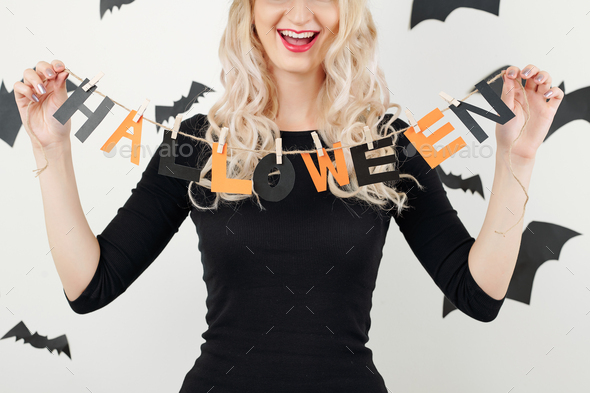Cheerful woman showing Halloween garland - Stock Photo - Images