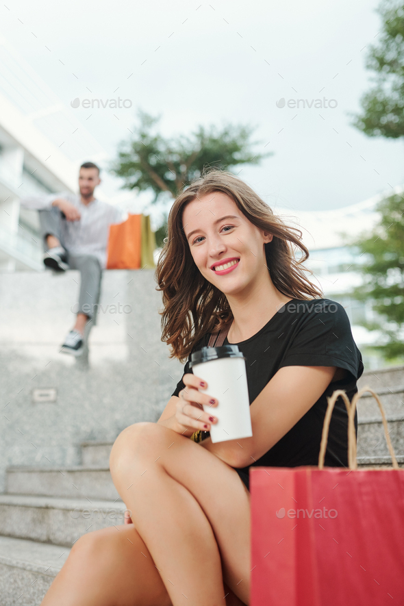 Cheerful young woman resting after shopping - Stock Photo - Images