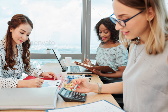 Businesswomen working at big office desk - Stock Photo - Images