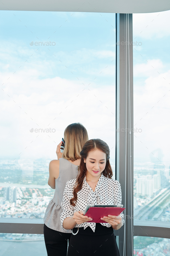 Young businesswoman reading financial report - Stock Photo - Images