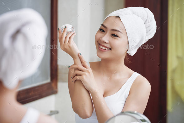 Happy young woman applying lotion - Stock Photo - Images
