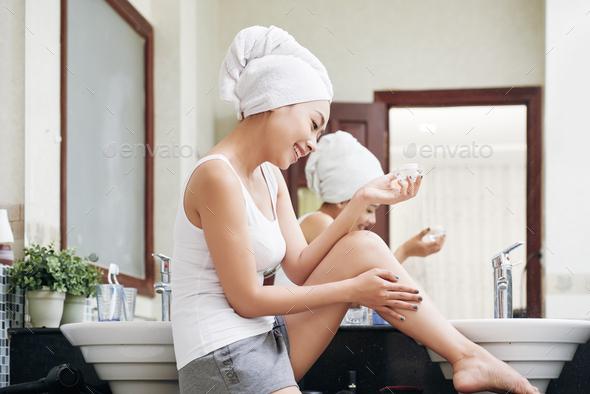 Ethnic woman moisturizing skin with lotion - Stock Photo - Images