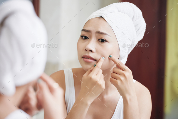 Asian woman popping pimples in mirror - Stock Photo - Images
