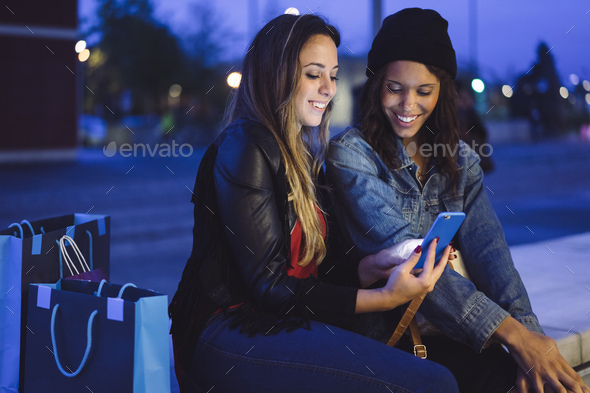 two young female friends chatting and looking at their mobile phone - Stock Photo - Images