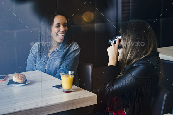 two female caucasian and african american friends having a coffee and taking picture - Stock Photo - Images