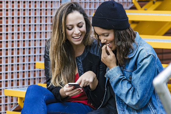 two mixed race female friends sitting and using a smartphone - Stock Photo - Images