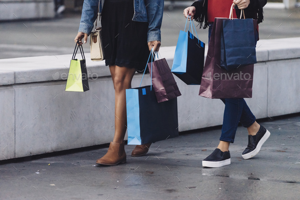 two female friends doing shopping downtown, full of shopping bags - Stock Photo - Images