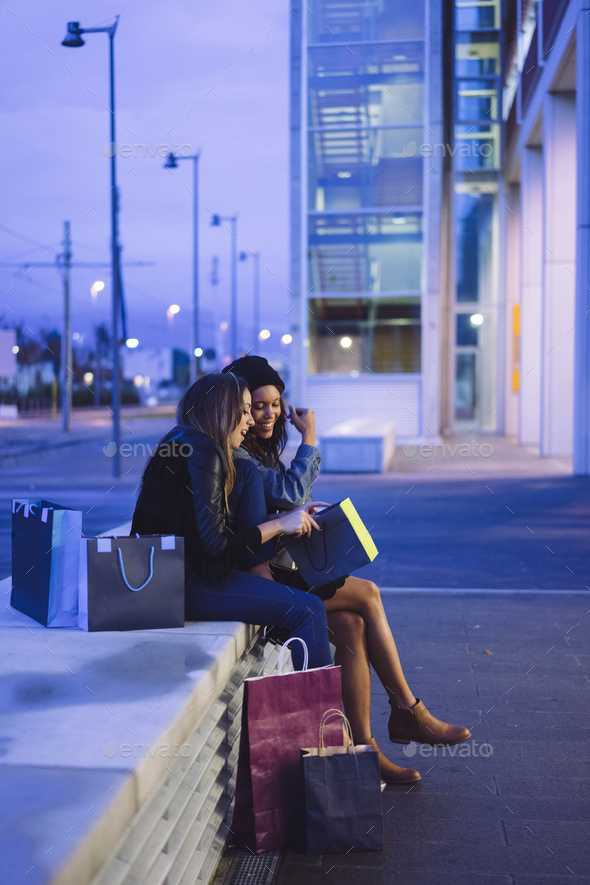 two female friends doing shopping in a city at night - Stock Photo - Images