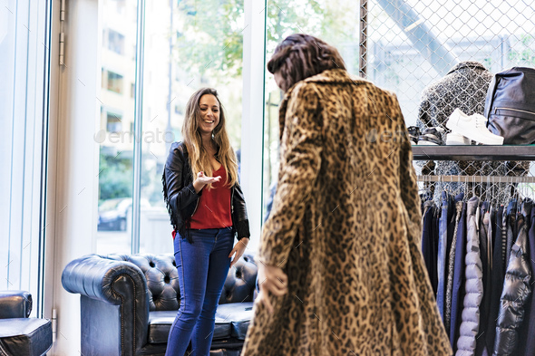 two mixed race female friends buying clothes in a store and having fun - Stock Photo - Images