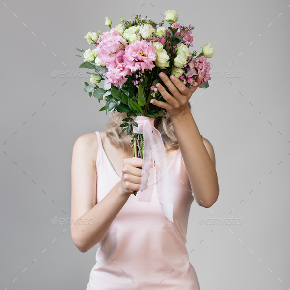 Woman Holding Bouquet In Hands And Hiding Her Face. - Stock Photo - Images