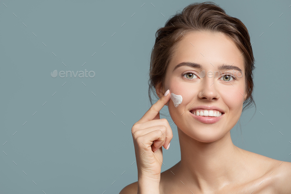 Portrait Of Beautiful Woman Applying Cream On Her Face. - Stock Photo - Images