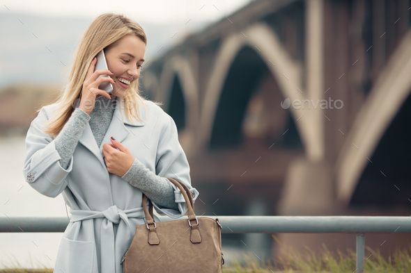 Young Woman In Blue Coat Talking Phone. Autumn City Background. - Stock Photo - Images