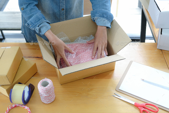 Online sellers are packing products into boxes for shipping to customers. - Stock Photo - Images
