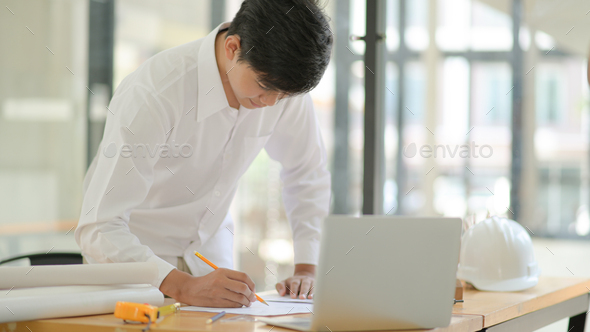 Architect used a pencil to draw on plan and plan the construction of the building for the client. - Stock Photo - Images