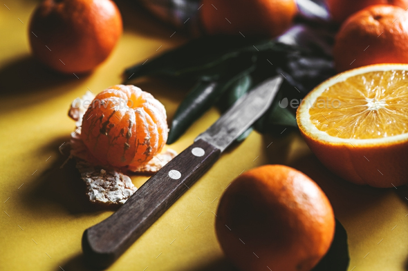 Fresh clementines, oranges on board with green leaves with a knife. Top view on a yellow background - Stock Photo - Images