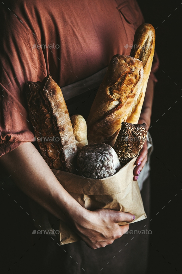 French baguettes in female hands on a black background. homemade baking - Stock Photo - Images