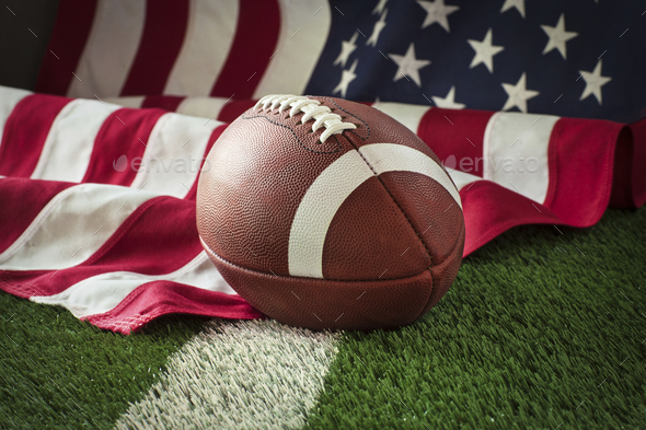 Football and American flag on green field - Stock Photo - Images