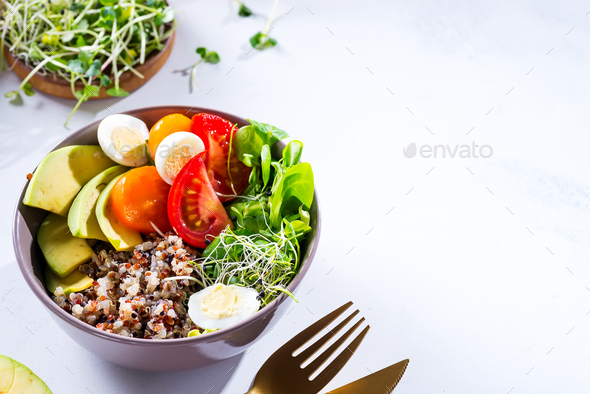 Fresh healthy salad with quinoa, cherry tomatoes and mixed greens, avocado, egg and micro greens on - Stock Photo - Images