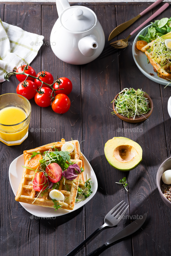 Belgian Waffles with avocado, eggs, micro green and tomatoes with orange juice and tea on wooden - Stock Photo - Images