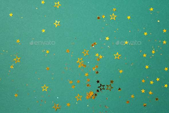 Golden star sparkles on green background - Stock Photo - Images