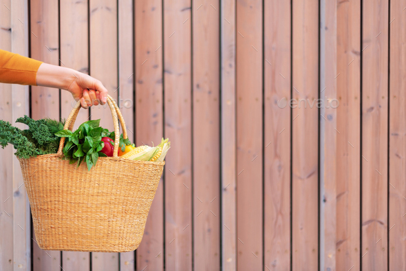 Girl holding basket with healthy organic vegetables, wooden background, copy space. Autumn harvest - Stock Photo - Images